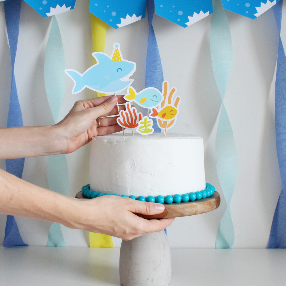 decorating a cake with a printable shark cake topper from my party design