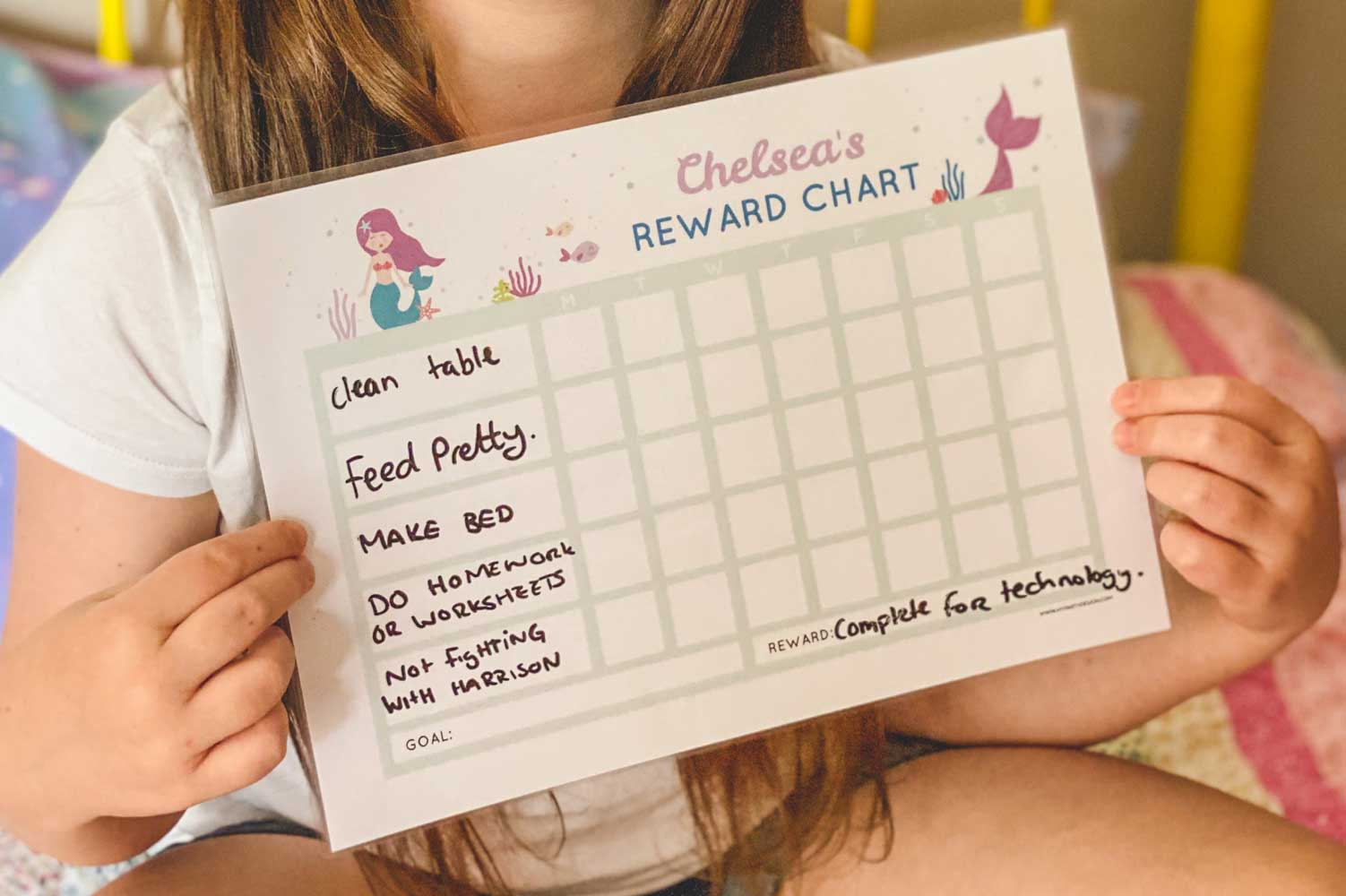 Young girl holding a reward chart for kids